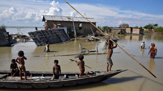 Children row a boat as they pass through damaged houses at a flood-affected village in Morigaon district