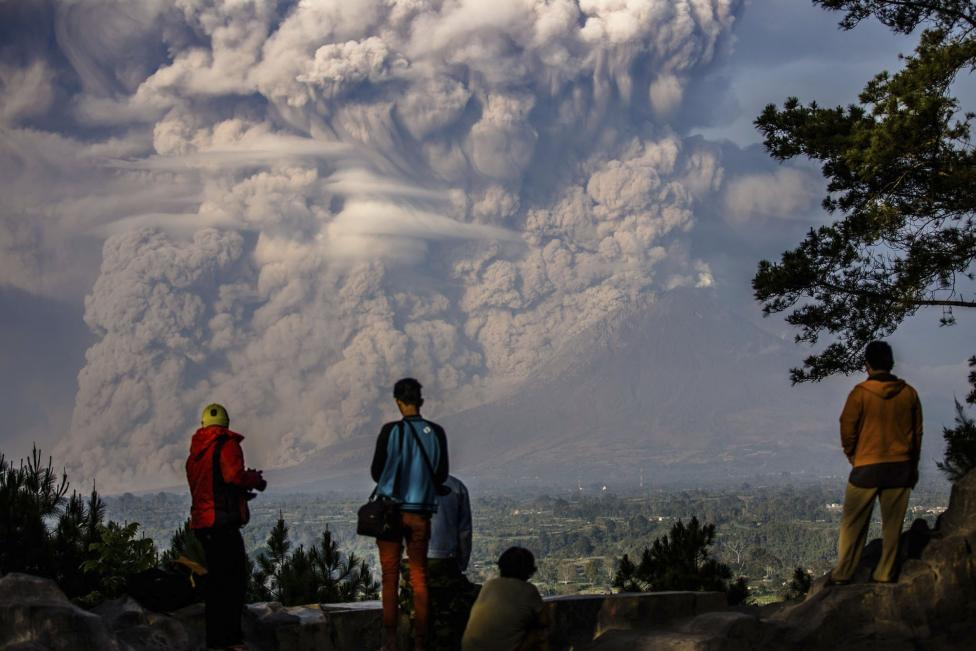 People watch as Mt. Sinabung ejects ash into the air during an eruption in Karo regency, Indonesia's North Sumatra province